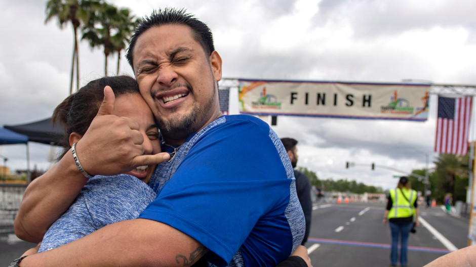 """Fernando Escobar is overcome with emotion after finishing his first half marathon in Tustin on Sunday, March 3, 2019. Nine months ago Escobar was living under a bridge in Redlands, addicted to methamphetamine and alcohol. """"I feel like I defeated a monster,"""" he said of finishing the race. He hugs Angelina Cabrera. Both are living at the OC Rescue Mission's Village of Hope. (Photo by Mindy Schauer, Orange County Register/SCNG)"""